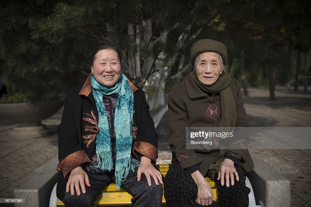Women pose for a photograph at Baotu Springs in Jinan, China, on Wednesday, Nov. 6, 2013. The third plenary session of the 18th Communist Party of China Central Committee will be held from Nov. 9 to Nov. 12 in Beijing. Photographer: Brent Lewin/Bloomberg via Getty Images