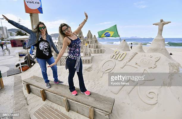 Women pose in front of sand sculptures of Vinicius the official mascot of the Rio de Janeiro Olympics and the 'Christ the Redeemer' statue at...