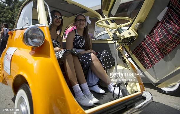 Women pose inside a 1962 BMW Isetta 300 during the classic cars parade in the framework of the Flower Festival in Medellin Antioquia department...