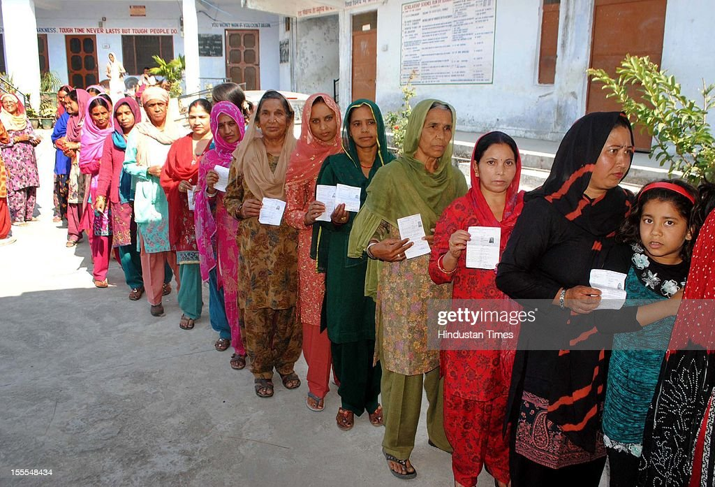 Women pose with their identification papers as they queue at a polling station to cast their vote in the Himachal Assembly election in Sakoh village near Dharamsala, on November 04, 2012 in Himachal Pardesh, India. Voting figures have indicated a high percentage turnout for polling in the assembly election.