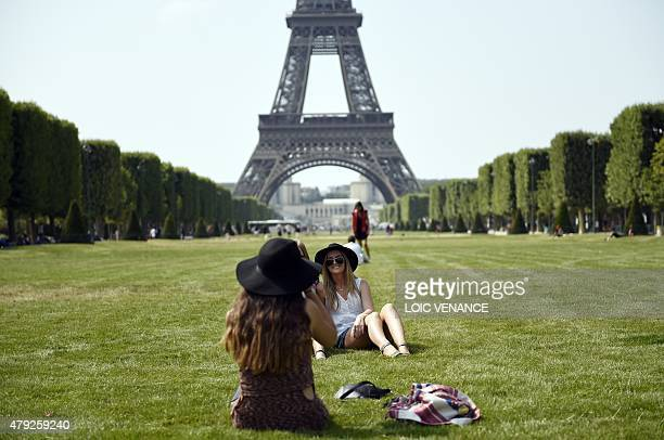 A women poses for a photograph in front of the Eiffel Tower on July 2 2015 in Paris AFP PHOTO / LOIC VENANCE