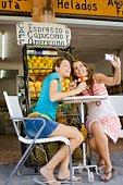 Women posing for digital camera at cafe