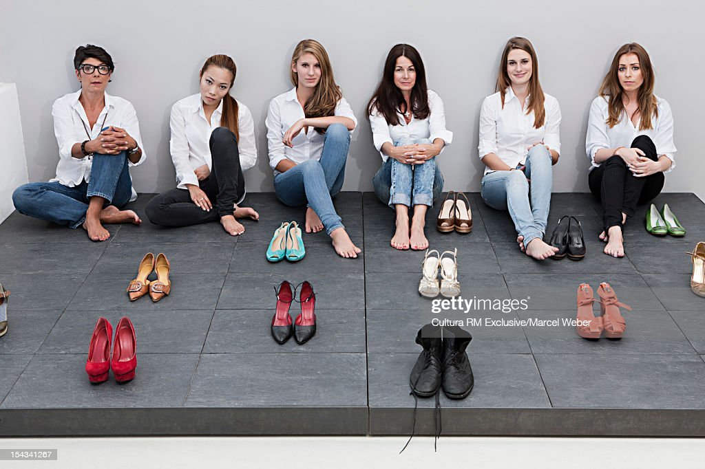 Women posing with pairs of shoes : Stock Photo