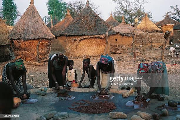 Women pounding shea nuts in a village near the monastery in Koubri Burkina Faso