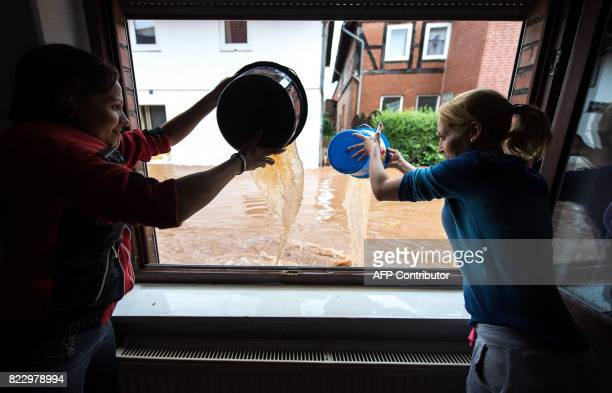 Women pour water out of a house in Rhueden northern Germany on July 26 2017 Some parts of lower saxony are overflooded after heavy rainfall / AFP...