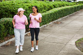 Senior woman (60s) with friend (40s) power walking together.