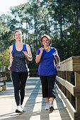 Multi-ethnic, mature women (50s) power walking in the park.