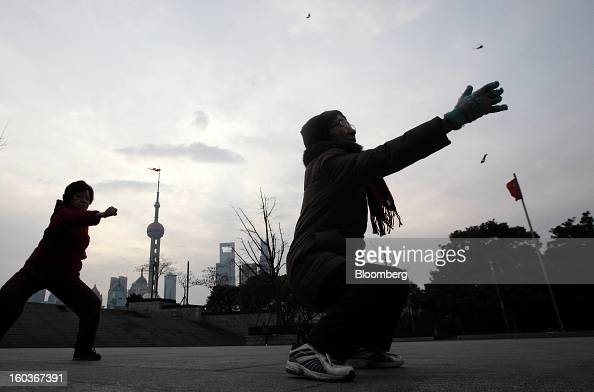 Women practice Tai Chi on the Bund as commercial buildings stand in the Pudong area background in Shanghai China on Tuesday Jan 29 2013 China's...
