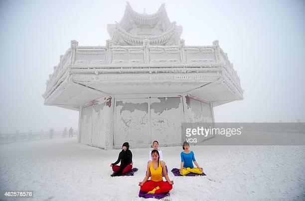 Women practice Yoga at the tianmen mountain scenic spot on January 31 2015 in Zhangjiajie Hunan province of China The temperature in Zhangjiajie is...