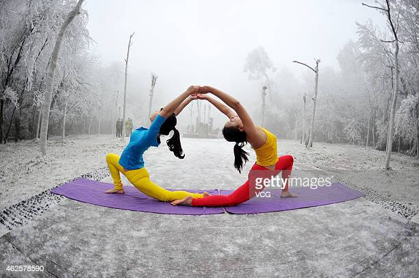 Women practice Yoga at the tianmen mountain scenic spot on January 31 2015 in Zhangjiajie Hunan province of China The temperature in Zhangjiajie is...