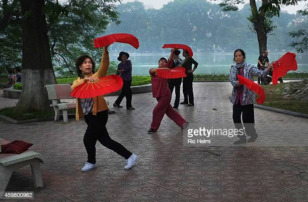 Women practicing martial arts fan dance on the shores of Hoan Kiem Lake near the Old Quarter in Hanoi