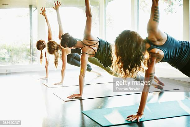 Women practicing yoga in side plank pose in class