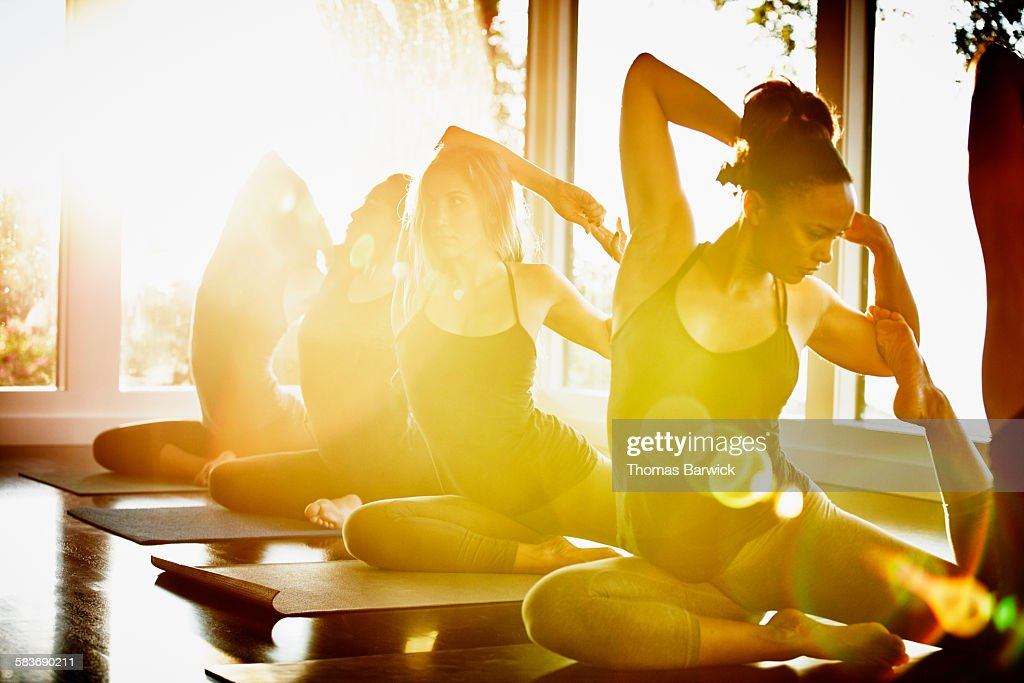Women practicing yoga in studio in mermaid pose
