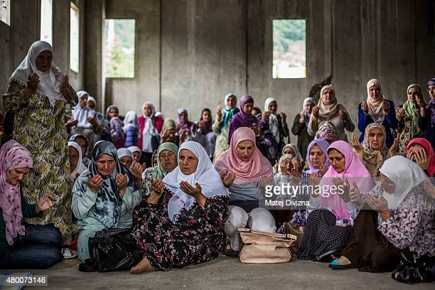 Women pray in the hall at the Potocari cemetery and memorial near Srebrenica on July 9 2015 in Srebrenica Bosnia and Herzegovina The newlyidentified...