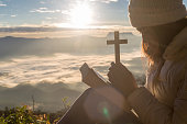 Women pray to god with the cross on the mountain background with morning sunrise. Woman Pray for god blessing to wishing have a better life. Christian life crisis prayer to god.