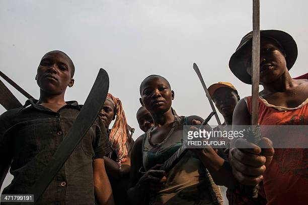 Women presenting themselves as antibalaka and 'Amazons' protecting their island from the members of the exSeleka pose with machetes on the Mbongo Soa...