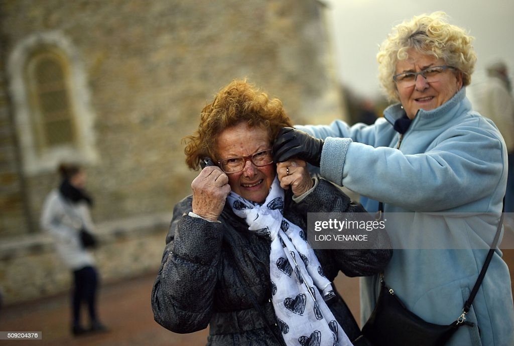 Women protect themselves against the wind in Les Sables-d'Olonne, western France, on February 9, 2016. High winds buffeted northwestern Europe on February 8, leaving one woman in France in a coma after she was hit by an advertising hoarding. Electricity was cut to 5,000 homes in northern France. / AFP / LOIC VENANCE