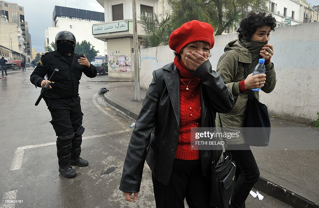 Women protect themselves from tear gas smoke during clashes between Tunisian police and protesters following a rallye outside the Interior ministry to protest after Tunisian opposition leader and outspoken government critic Chokri Belaid was shot dead, on February 6, 2013 in Tunis. The protesters, who massed on Habib Bourguiba Avenue, epicentre of the 2011 uprising that ousted ex-dictator Zine El Abidine Ben Ali, pelted the police with bottles and the police responded by firing tear gas, chasing the protesters and beating them with batons.