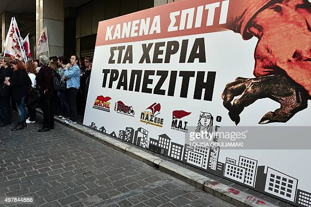 Women protest next to a huge banner reading 'No house in the hands of bankers' on November 19 outside of the finance ministery in Athens ahead of a...