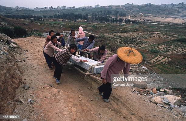 Women push a cart loaded with a granite block away from a quarry near Chong Wu town Hui'An county