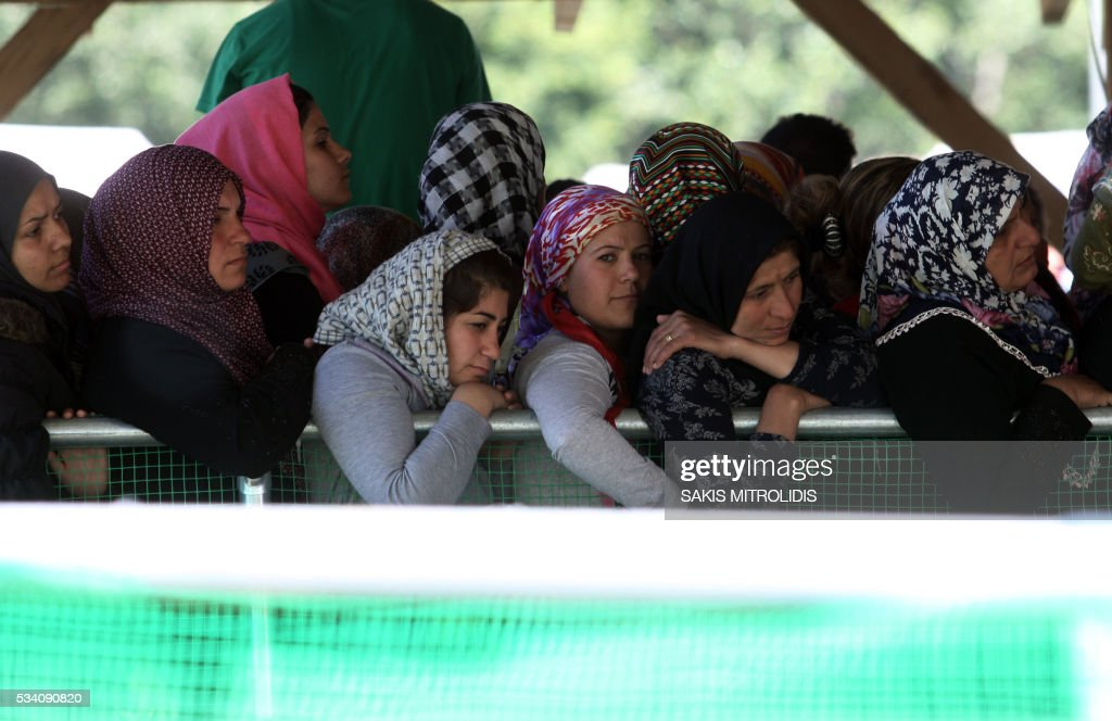 Women queue for food at a gas station some 20 km from the Greek-Macedonian border, on 25 May, 2016 in Polykastro. In an operation which began shortly after sunrise on May 24, hundreds of Greek police began evacuating the sprawling camp which is currently home to 8,400 refugees and migrants, among them many families with children, an AFP correspondent said. At its height, there were more than 12,000 people crammed into the site, many of them fleeing war, persecution and poverty in the Middle East and Asia, with the camp exploding in size since Balkan states began closing their borders in mid February in a bid to stem the human tide seeking passage to northern Europe. / AFP / SAKIS