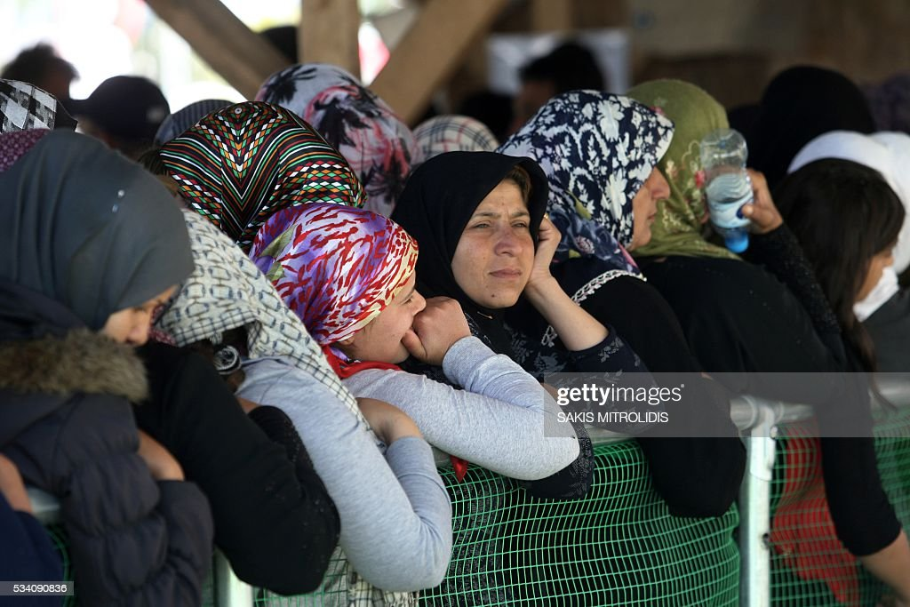 Women queue for food at a makeshift camp set near a gas station some 20 km from the Greek-Macedonian border, on 25 May, 2016 in Polykastro. In an operation which began shortly after sunrise on May 24, hundreds of Greek police began evacuating the sprawling camp which is currently home to 8,400 refugees and migrants, among them many families with children, an AFP correspondent said. At its height, there were more than 12,000 people crammed into the site, many of them fleeing war, persecution and poverty in the Middle East and Asia, with the camp exploding in size since Balkan states began closing their borders in mid February in a bid to stem the human tide seeking passage to northern Europe. / AFP / SAKIS