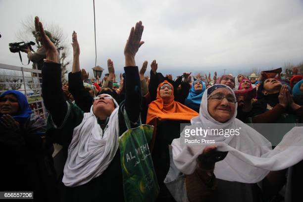 Women raise hands towards the holy relic being displayed by the priest of the famous Hazratbal Shrine in Indianadministered Kashmir's capital...