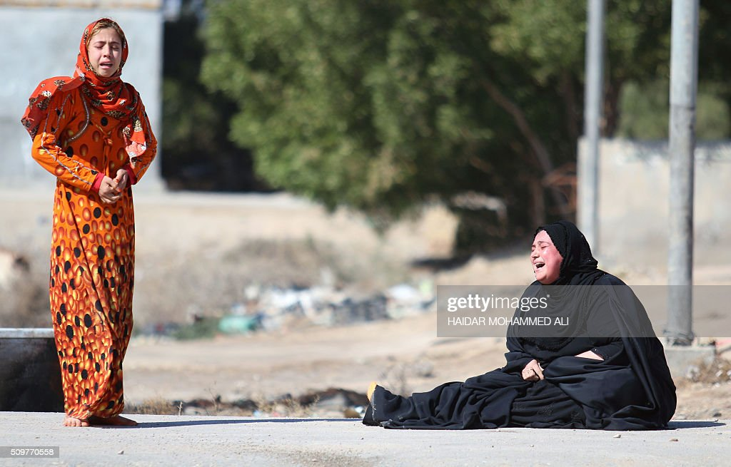 Women react after Iraqi security forces detained suspects in the Nahr al-Ezz area, 150km North of Basra, on February 12, 2016 during a security operation. Operations by the security forces, including the intelligence services, are regular in the area in an attempt to contain and disarm feuding local gangs and tribes. / AFP / HAIDAR MOHAMMED ALI