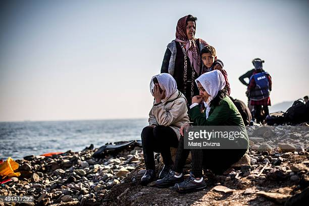 Women react as they arrive with other refugees and migrants on the shores of the Greek island of Lesbos after crossing the Aegean sea from Turkey on...