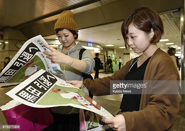 Women read an extra edition of a newspaper reporting on the retirement of Hiroshima Carp pitcher Hiroki Kuroda in the city of Hiroshima on Oct 18 2016