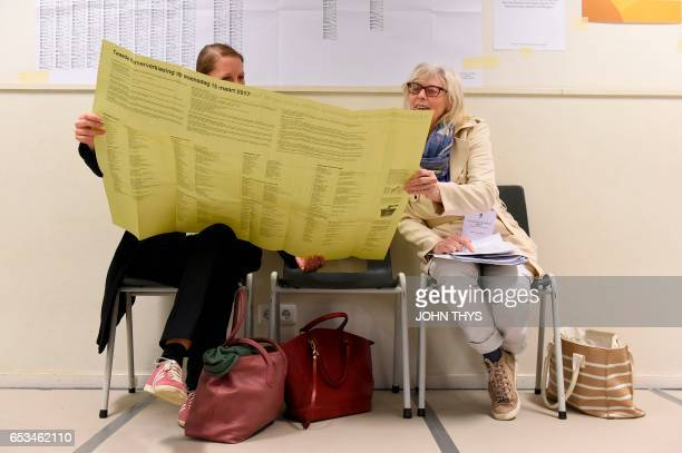 TOPSHOT Women read voting information at a polling station during Dutch general elections in The Hague on March 15 2017 Millions of Dutch voters were...