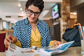 Photo of mature woman reading magazine in coffee shop