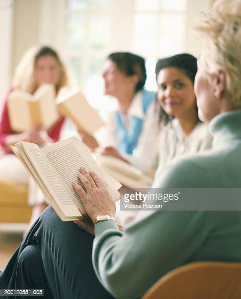 Women reading in book club, rear view, (focus on book)