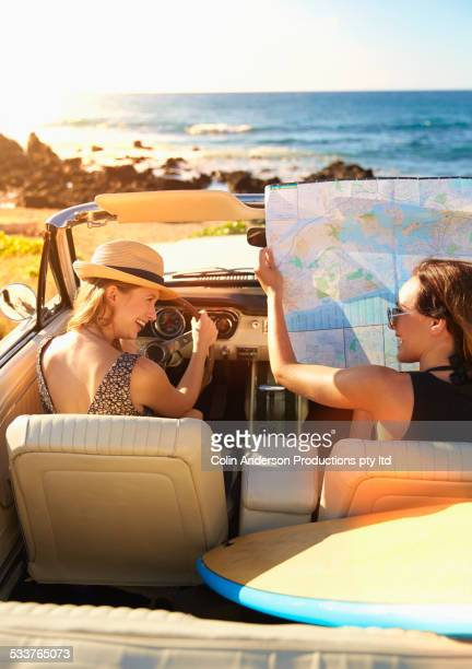 Women reading map in convertible on beach