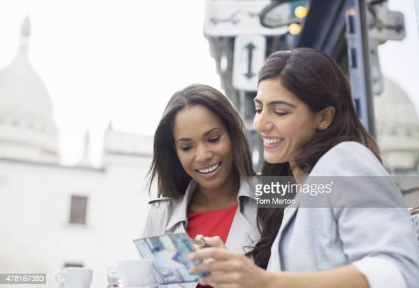 Women reading postcard at sidewalk cafe in Paris, France