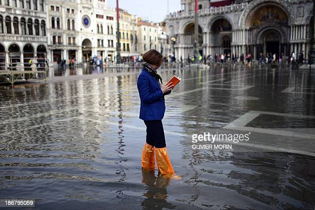 A women reads a book in the flooded Piazza San Marco on November 4 2013 in Venice Saint Mark's Square as the lowest point of Venice is always the...