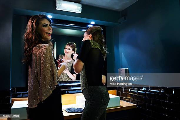 Women re-applying makeup in club toilets