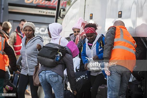 Women refugees surrounded by the staff of the association 'La Vie Active' carry their luggages as they walk to climb into a bus afterleaving the...