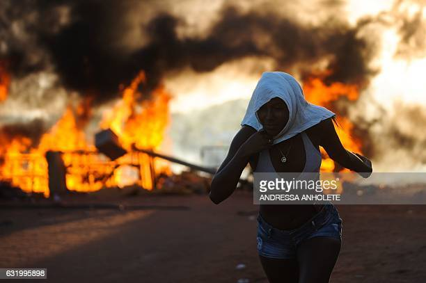TOPSHOT Women relatives of inmates set makeshift barricades on fire in protest for the transfer of some 200 prisoners from the Alcacuz Penitentiary...