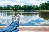 Pair of feet relaxing by a lake on a wooden dock. People relaxing.