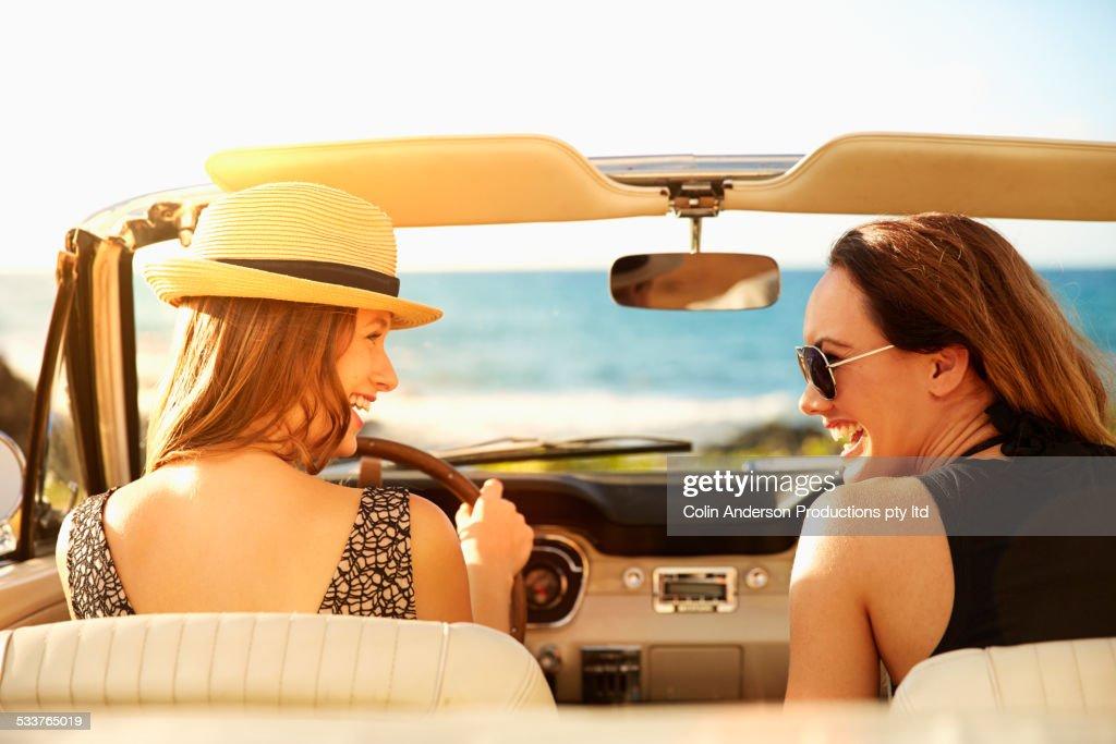 Women relaxing in convertible on beach
