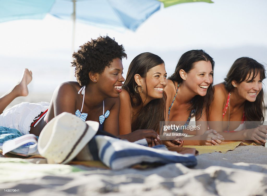 Women relaxing on beach blanket together : Stock Photo