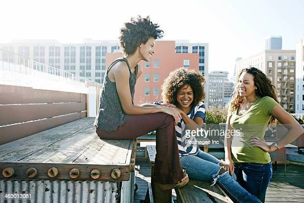 Women relaxing on urban rooftop