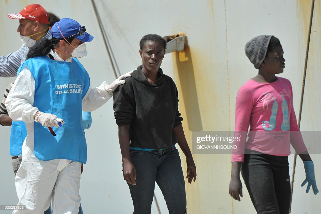 Women rescued at sea arrive aboard the Italian Navy ship 'Vega' on May 29, 2016 in the port of Reggio Calabria, southern Italy. A week of shipwrecks and death in the Mediterranean culminated today with harrowing testimony from migrant survivors who said another 500 people including 40 children had drowned, bringing the number of feared dead to 700. / AFP / GIOVANNI