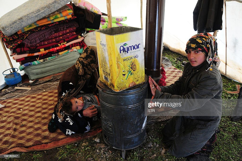 Women rest near a coal stove inside a tent at the Syrian refugee camp 5km from Diyarbakir, on the the way between Diyarbakir and Mardin, after snowfall, on January 9, 2013. The refugees faced further misery due to increasing shortages of supplies, low temperatures, and snowfall.