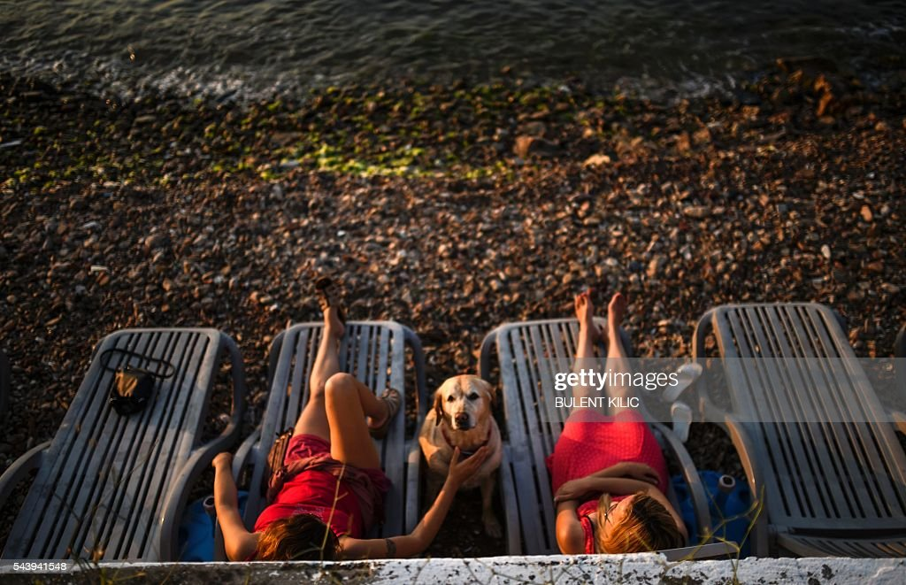 Women rest on the beach with their dog on June 30, 2016 in the Prince Islands in Istanbul. Turkey's already limping tourism industry is suffering a fresh grievous blow after the latest in a series of attacks targeted at tourists claimed dozens of lives, analysts said on June 29, 2016. / AFP / BULENT