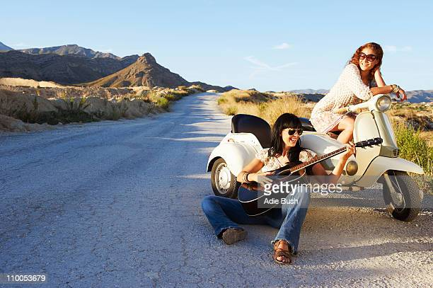 Women resting by road with motorbike