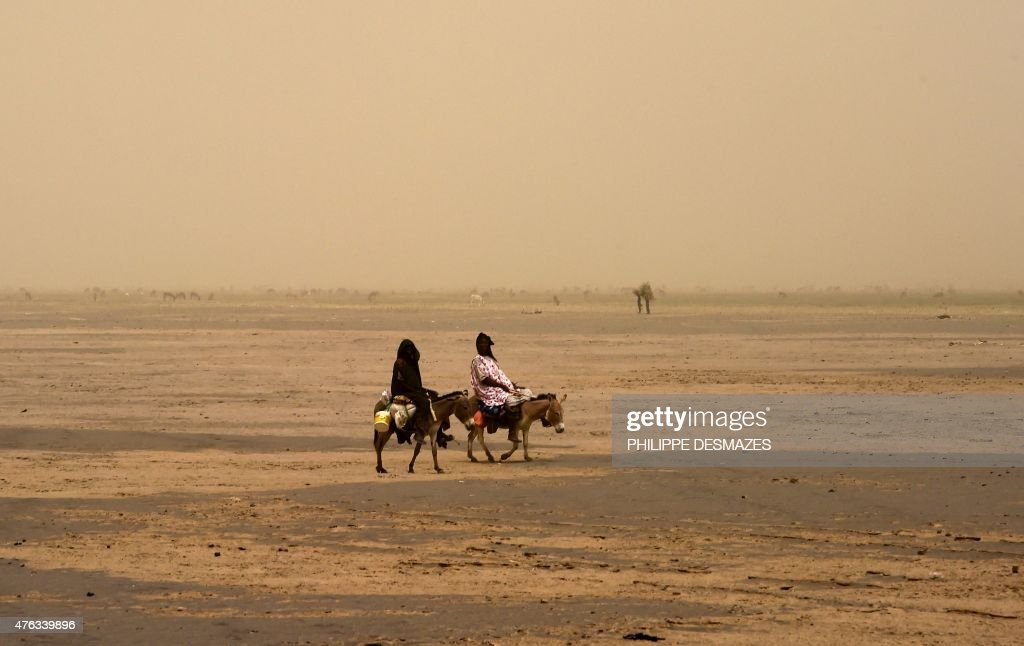 Women ride donkeys on June 4 2015 on the dry lake of Faguibine near Bintagoungou in the region of Timbuktu northern Mali while French soldiers of the...