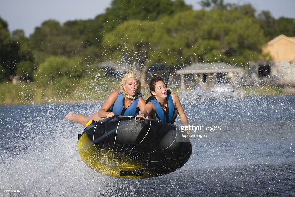 Women riding towable tube