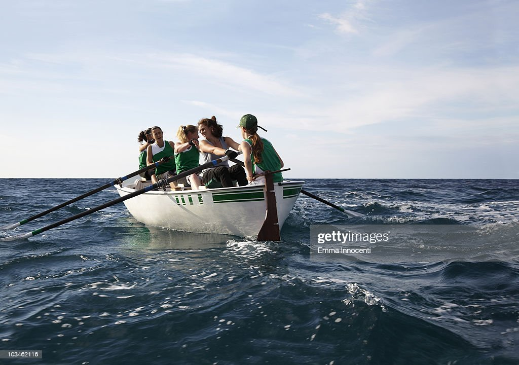 Women rowing team out at sea : Stock Photo